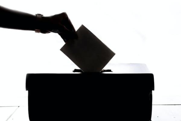 Silhouette of hand dropping ballot into box