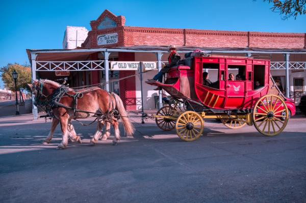 old western stagecoach in front of a brick building